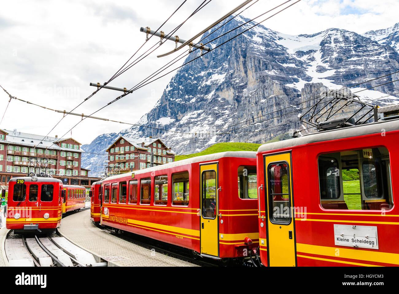 Mountain railway trains at Kleine Scheidegg above Grindelwald Switzerland with the Eiger behind - Stock Image
