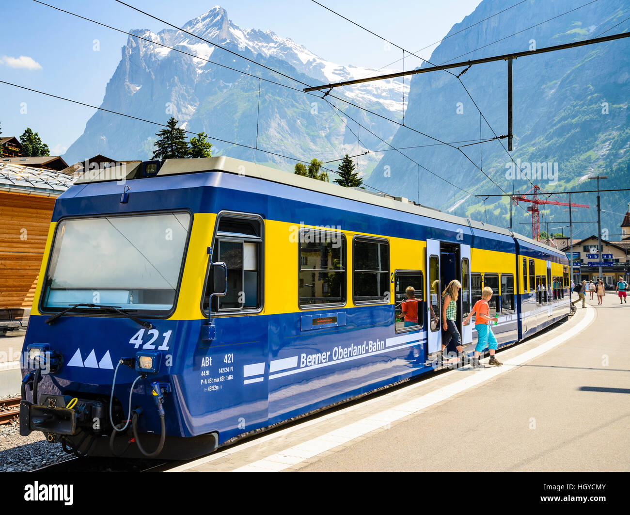 Children leave a train at Grindelwald Switzerland with the Wetterhorn peak behind - Stock Image