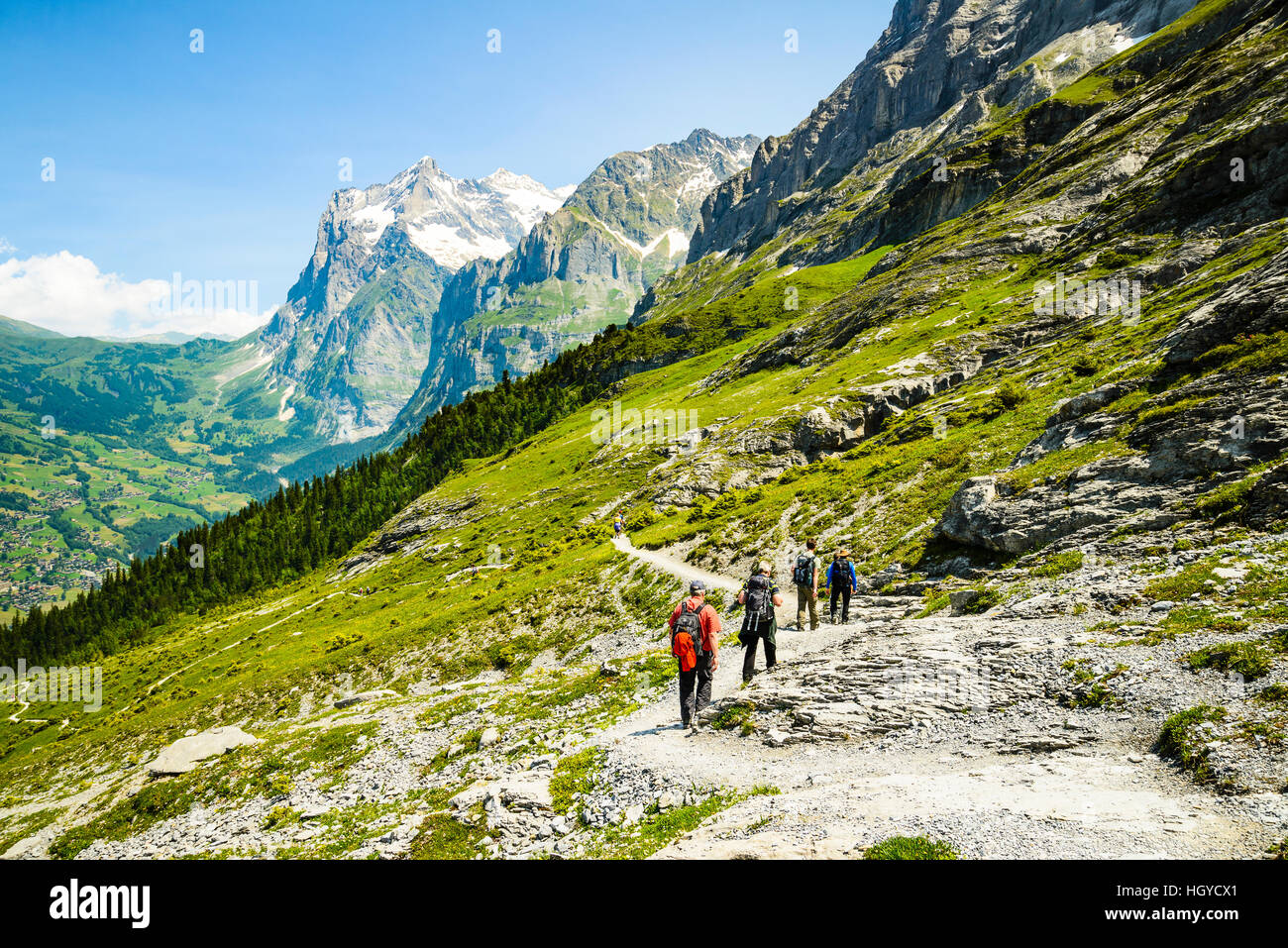 Hikers on the Eiger Trail Switzerland with the Grindelwald valley below and the Wetterhorn peak behind - Stock Image