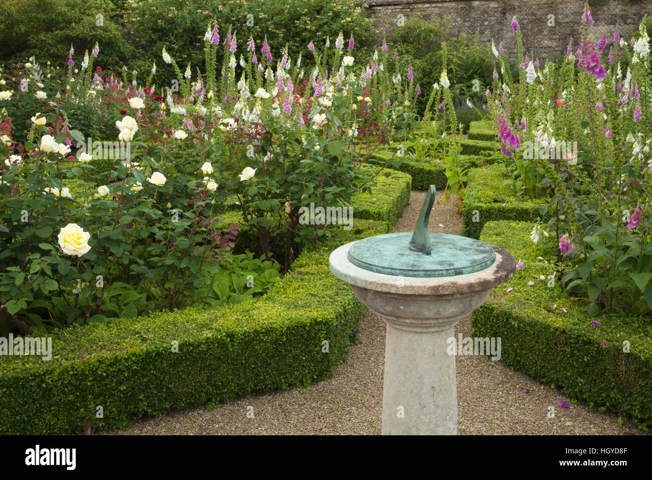 Ornamental sundial with foxgloves and roses in the parterre within the walled garden of Rousham House in Oxfordshire, - Stock Image