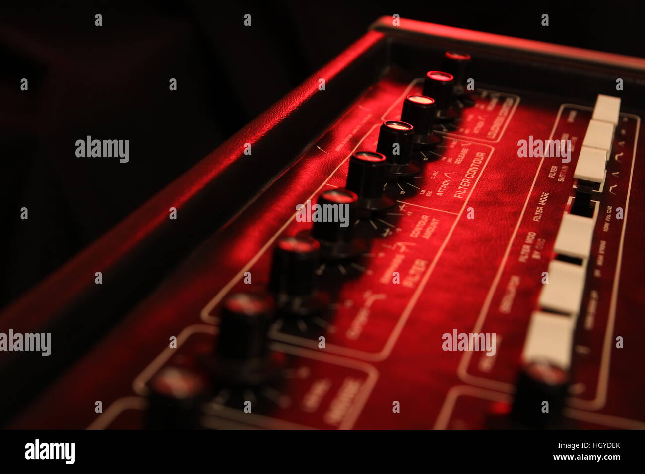 Controls of a retro analog music synth in red light - Stock Image
