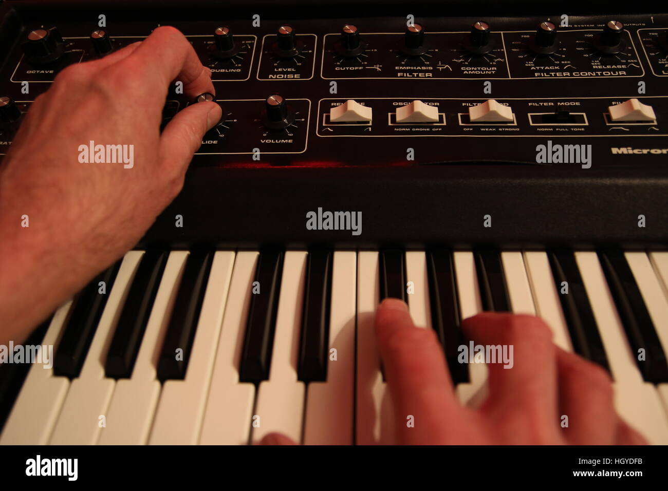 Man adjusting and playing vintafge analogue music synthesizer - Stock Image