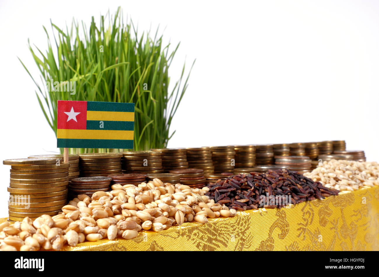 Togo flag waving with stack of money coins and piles of wheat and rice seeds - Stock Image