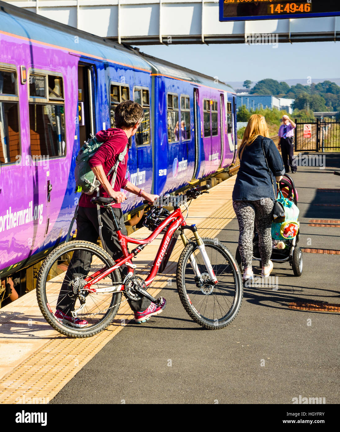Woman with bicycle disembarking from train at Buckshaw Parkway near Chorley Lancashire - Stock Image