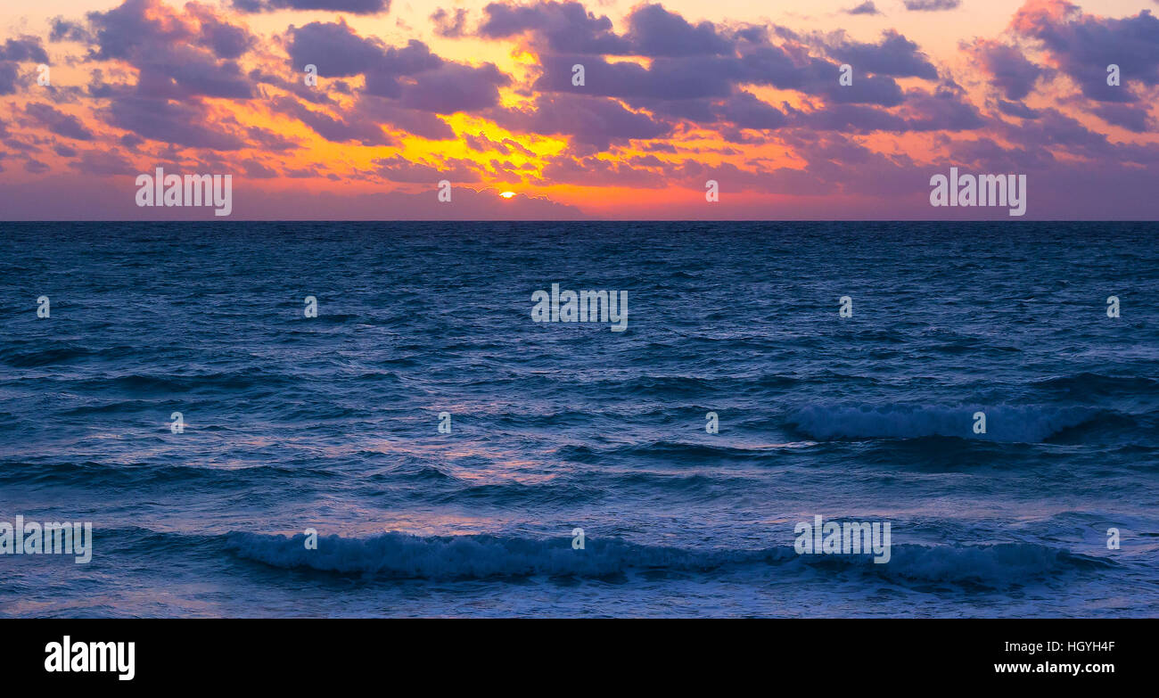 Sunset over the ocean with violet clouds. - Stock Image