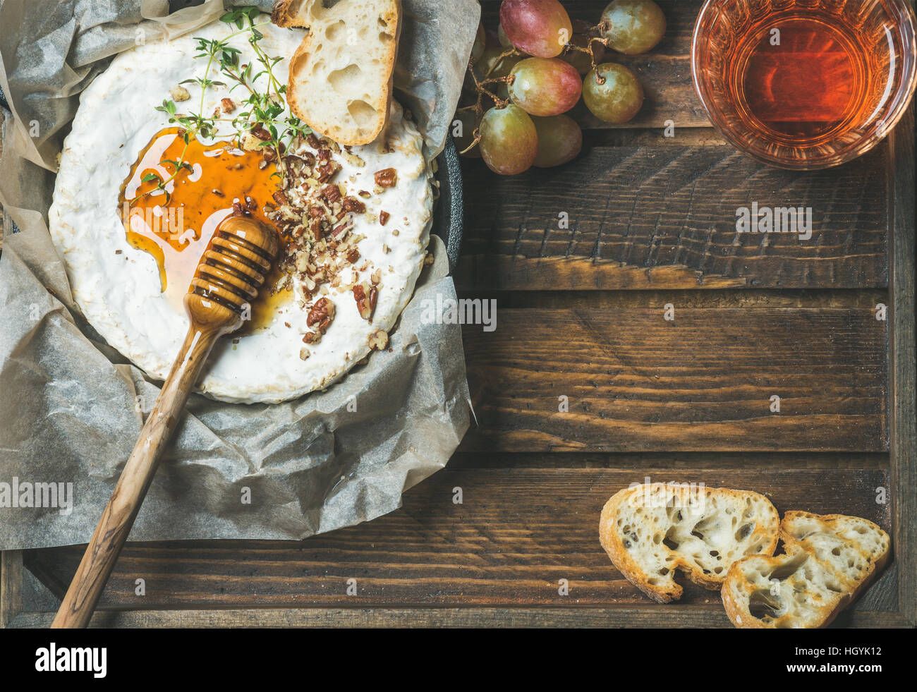Camembert , grapes, baguette slices and glass of rose wine - Stock Image