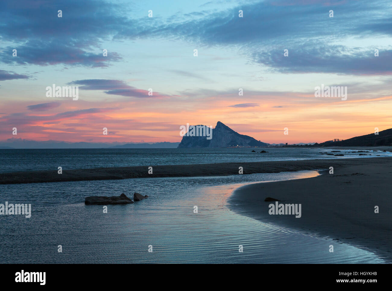 View of The Rock of Gibraltar and La Linea de la Concepcion as seen from the Mediterranean coast at sunset, Cadiz, Stock Photo
