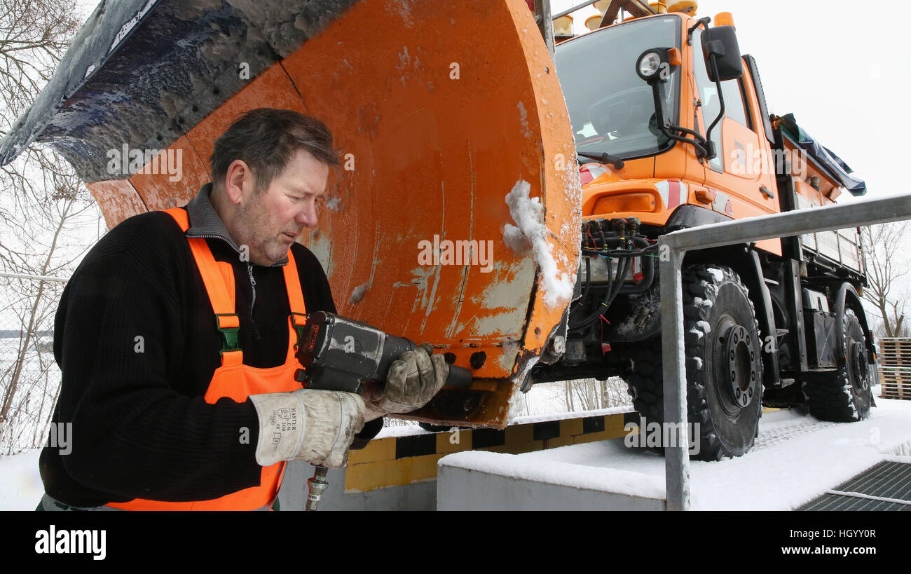 Riedlingen, Germany. 14th Jan, 2017. A winter service road crew worker changes a worn track on a snow plow in Riedlingen, - Stock Image