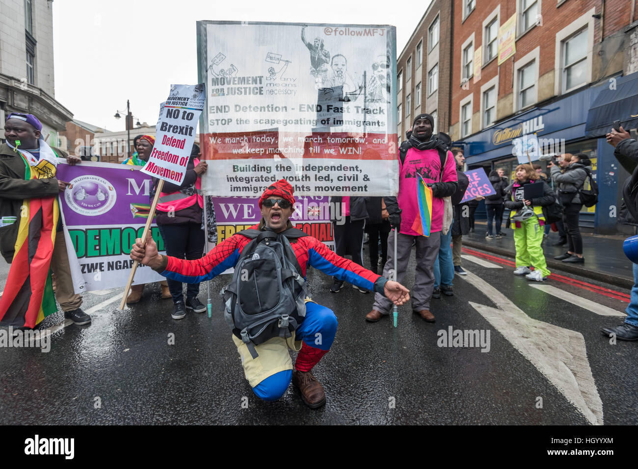 London, UK. 14th January 2017. A man poses in front of the Movement for Justic march in Brixton against mass deportations - Stock Image