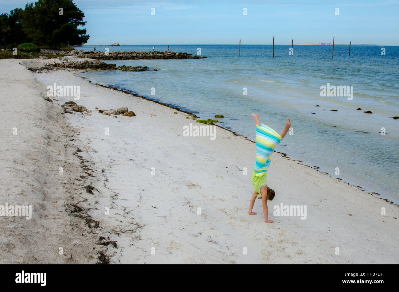 A child does a cartwheel on a white sand beach in Florida - Stock Image