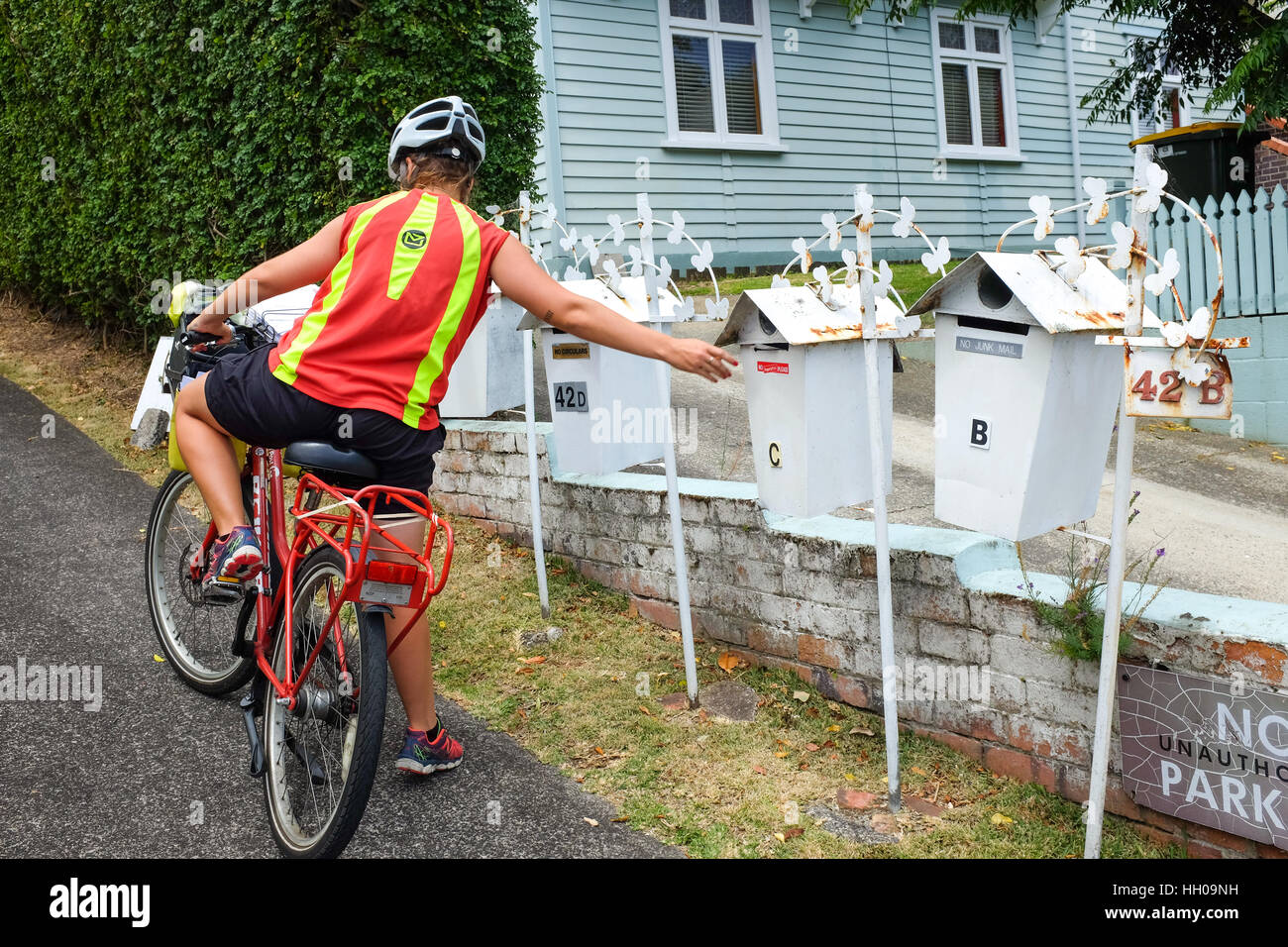 A postal worker in New Zealand delivering letters. - Stock Image