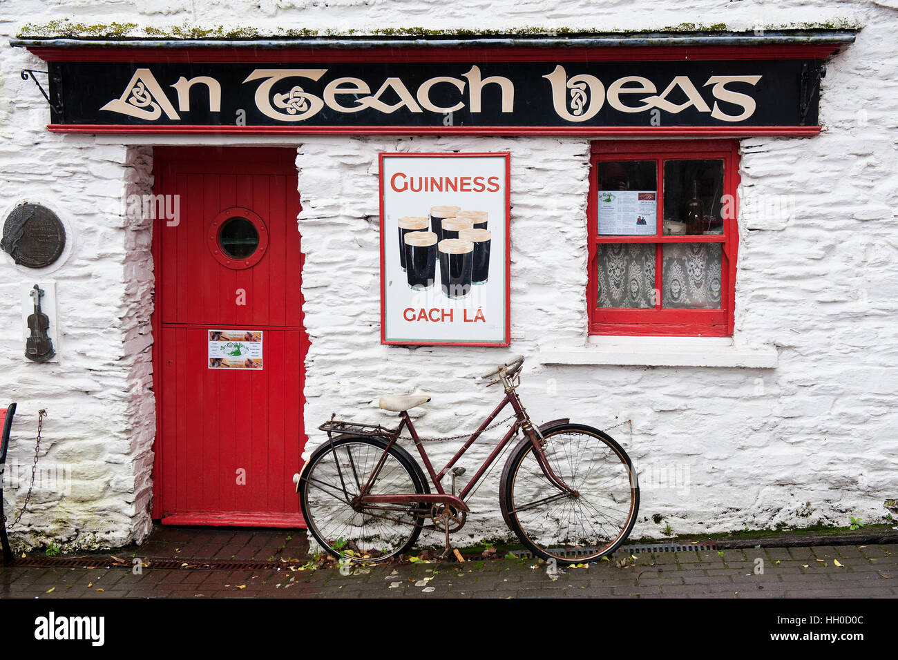 An Teach Beag, a small whitewashed pub with red door old bike in the town of Clonakilty, West Cork, Ireland part - Stock Image