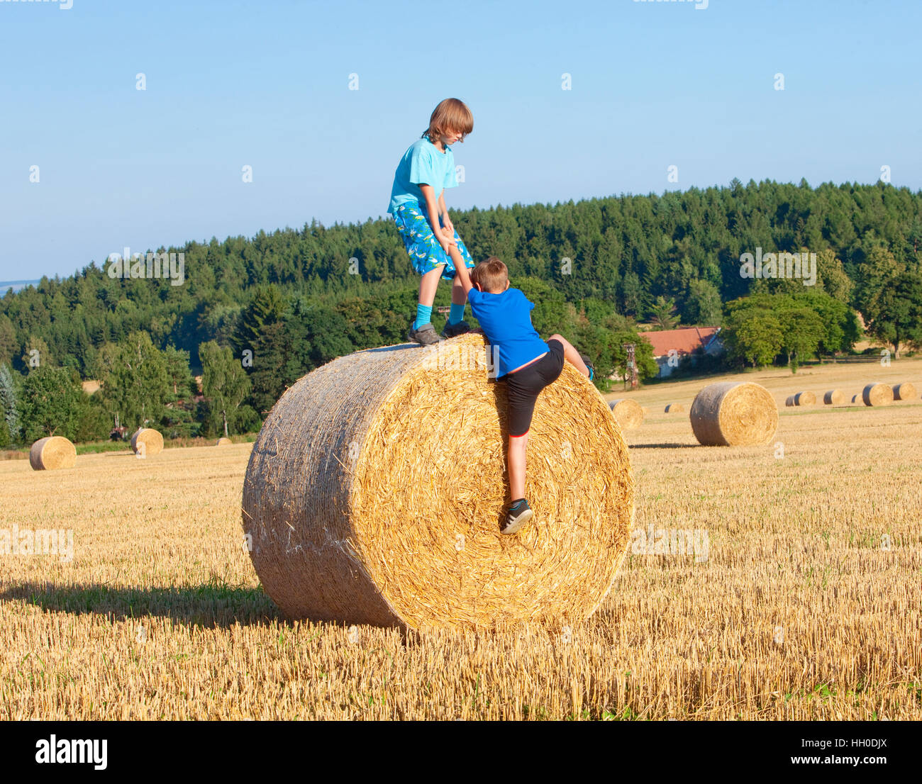 Two Boys Helping Each Other to Climb a Bale of Hay - Stock Image