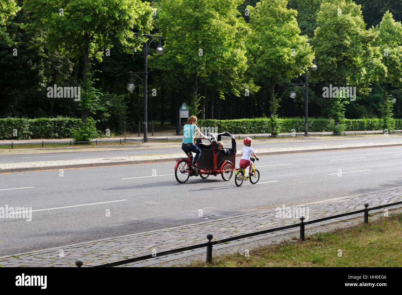 A mother and two children traveling by bicycles on the road by the Tiergarten Park in Berlin, Germany. Stock Photo