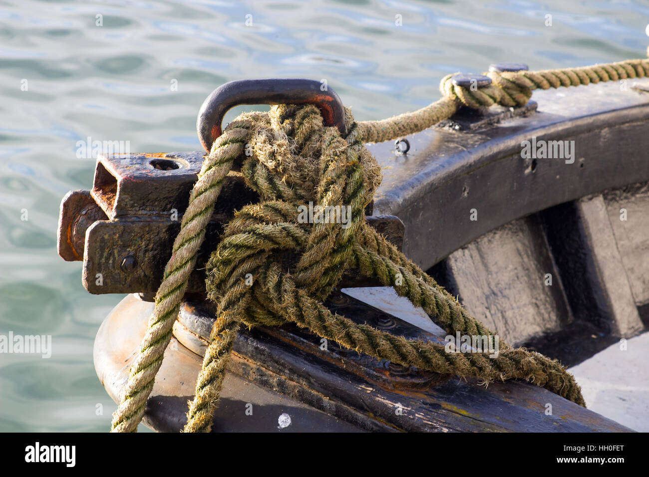 Knotted rope around a mooring bollard on a small trawler bow - Stock Image