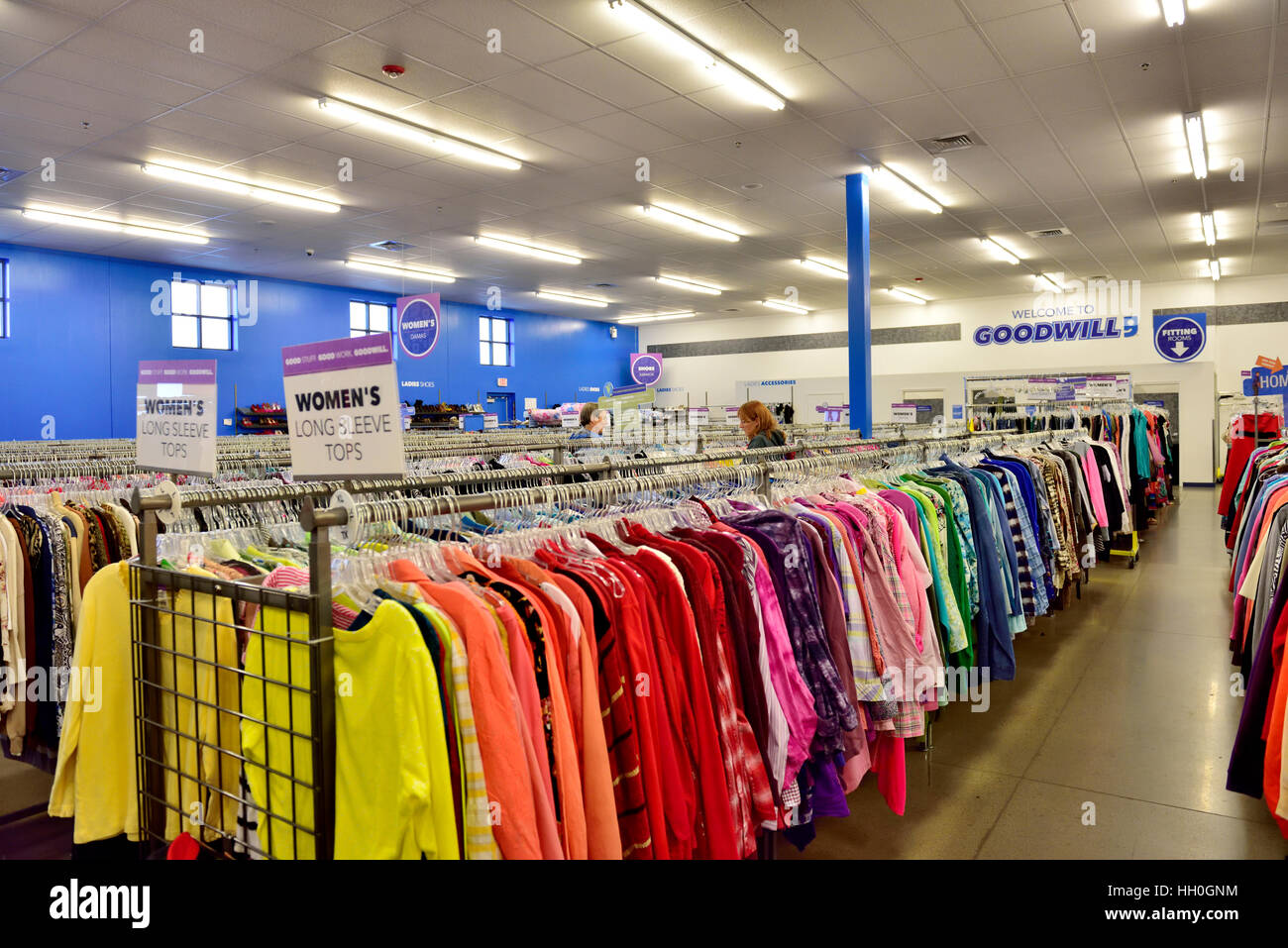 Rack of colorful woman's shirts for sale in a Goodwill store - Stock Image