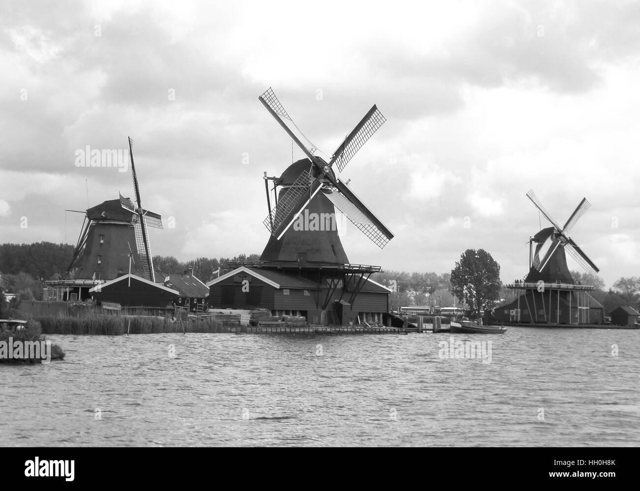 Three waterfront Dutch windmills under the cloudy sky, Zaanse Schans, Netherlands, Monochrome photo - Stock Image
