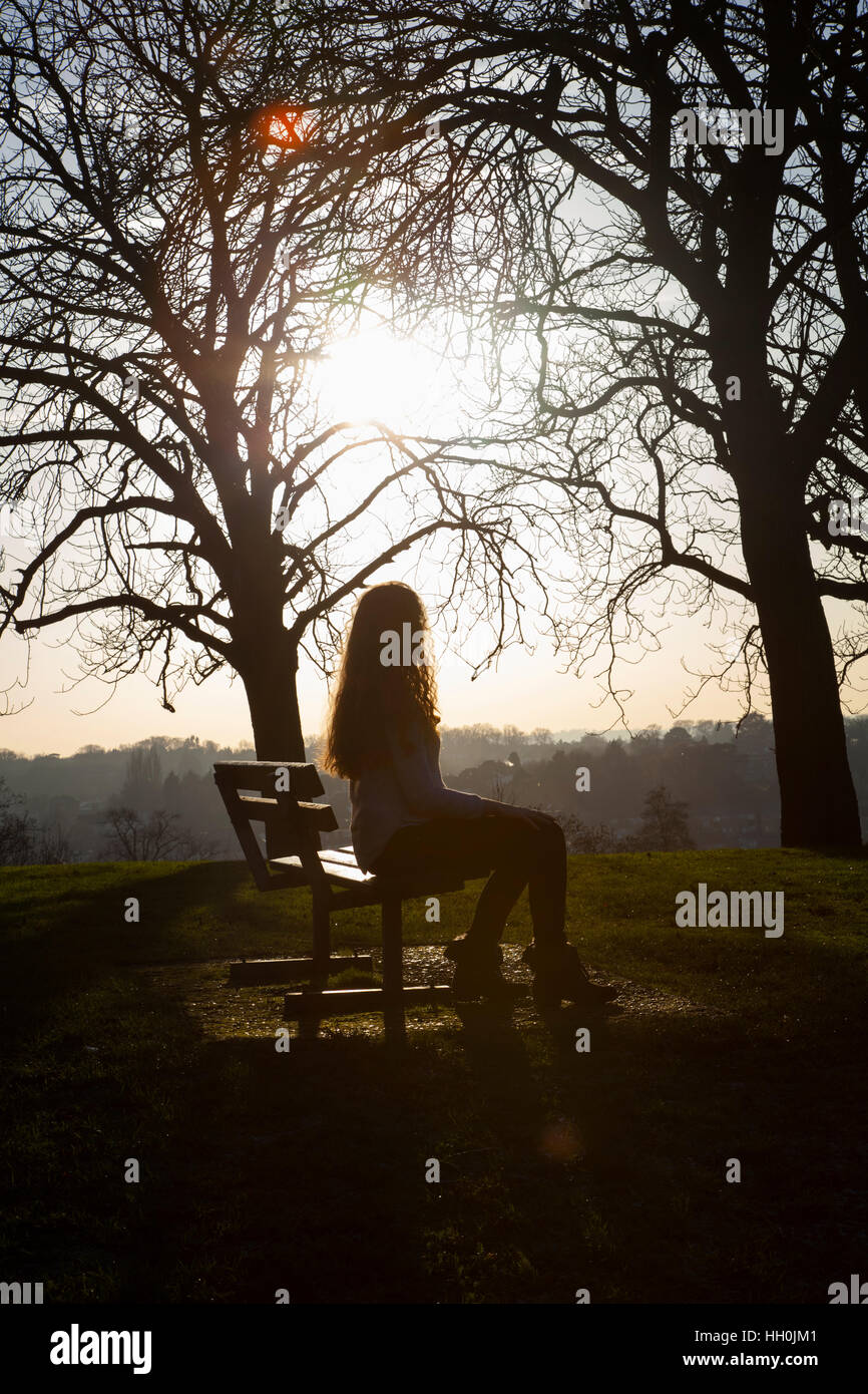 Silhouette of a back view of a woman sitting alone on a bench in a ... for bench silhouette back  155sfw