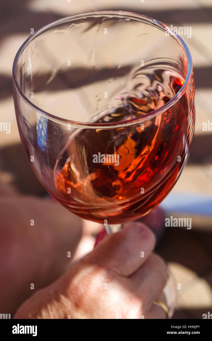 Glass of Rose wine being swirled with hand in shot - Stock Image