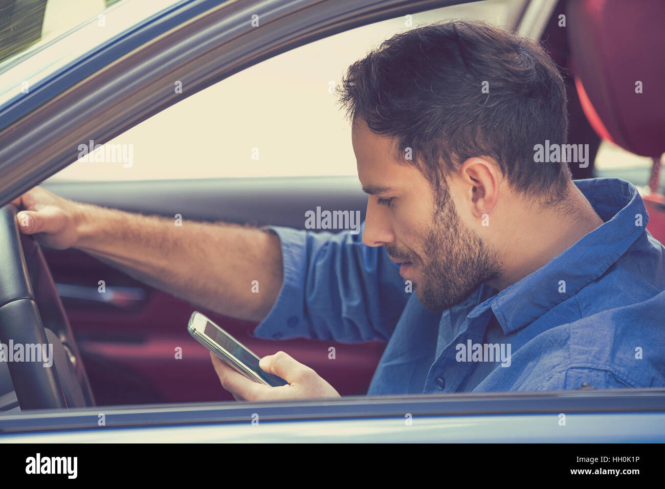 Portrait of handsome young business man using texting on mobile phone while driving a car Stock Photo