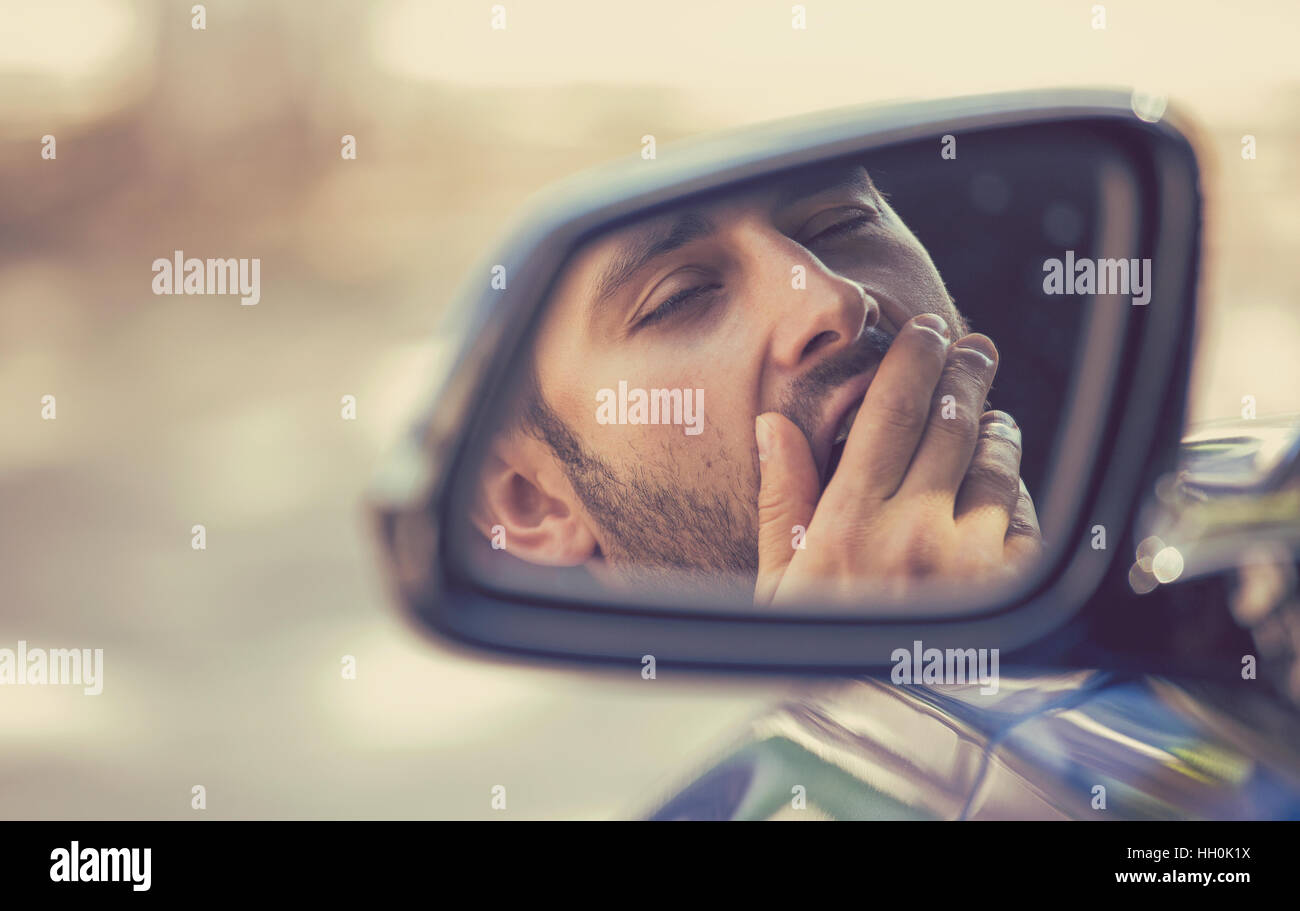 Side mirror view reflection sleepy tired fatigued yawning exhausted young man driving his car in traffic after long - Stock Image