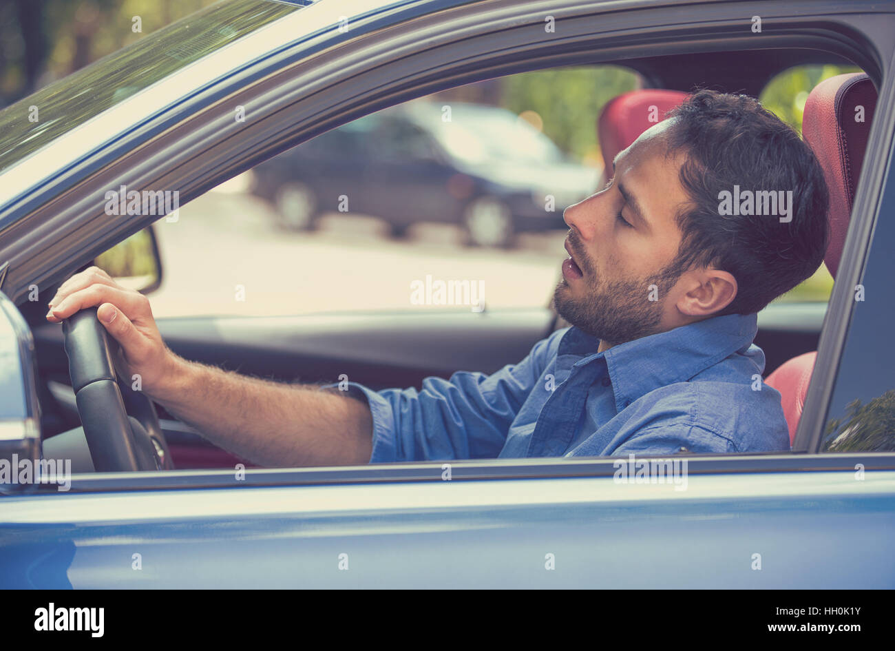 Side view sleepy tired fatigued exhausted man driving car in traffic after long hours. Transportation safety sleep - Stock Image