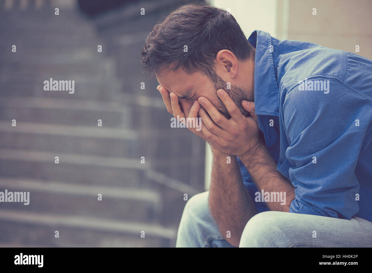 side profile stressed sad young crying man sitting outside holding head with hands looking down. Human emotion feelings Stock Photo