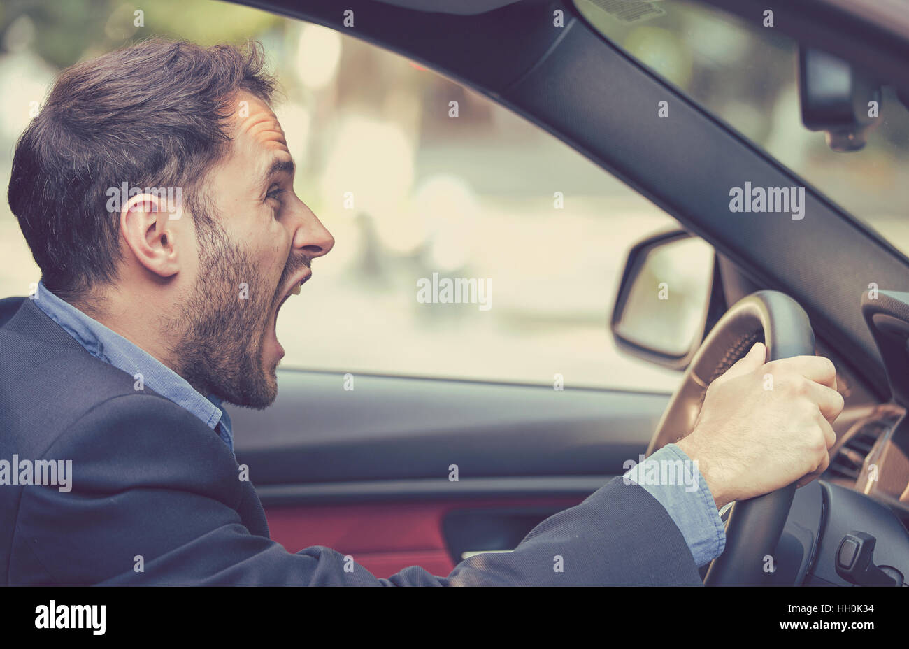 Side profile angry driver. Negative human emotions face expression - Stock Image