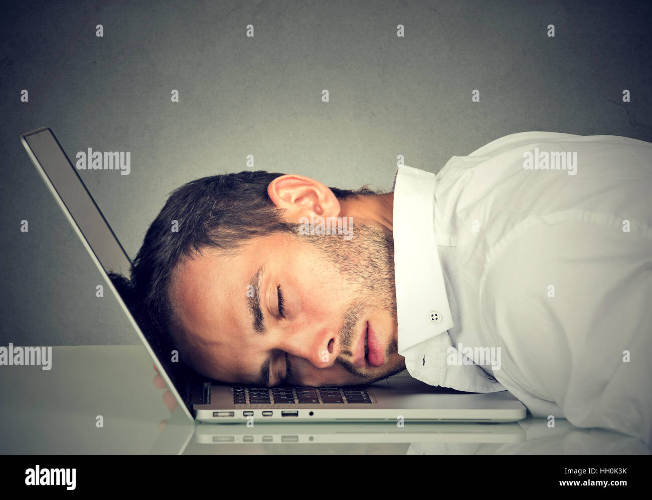 Business man sleeping on his laptop in his office - Stock Image