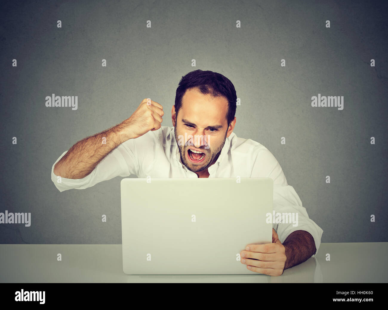Portrait angry business man working on the laptop. Negative human emotion face expression - Stock Image