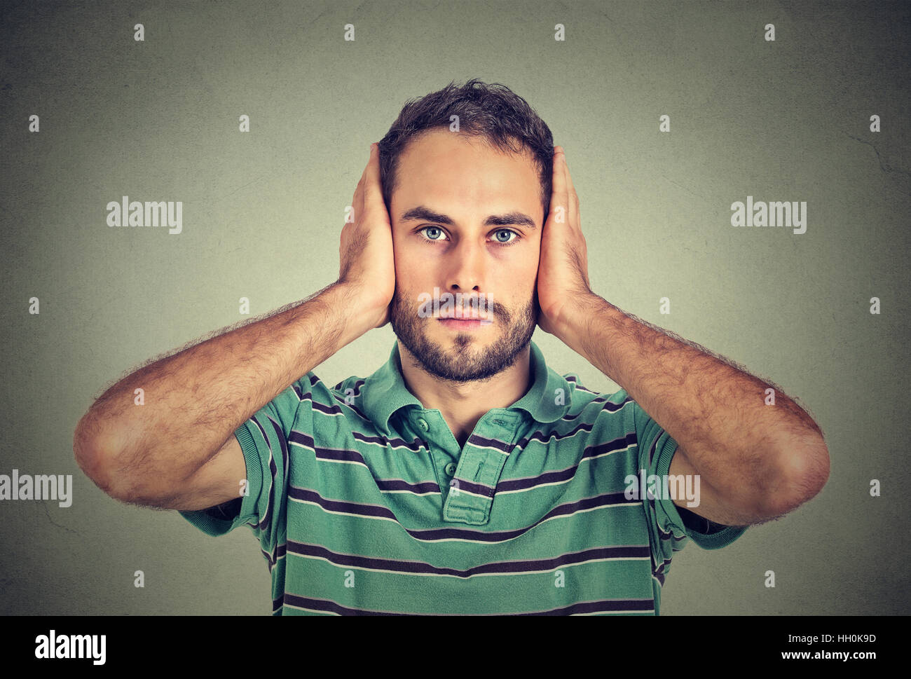 handsome, peaceful, tranquil, relaxed, young man covering his ears, observing isolated on gray wall background. - Stock Image