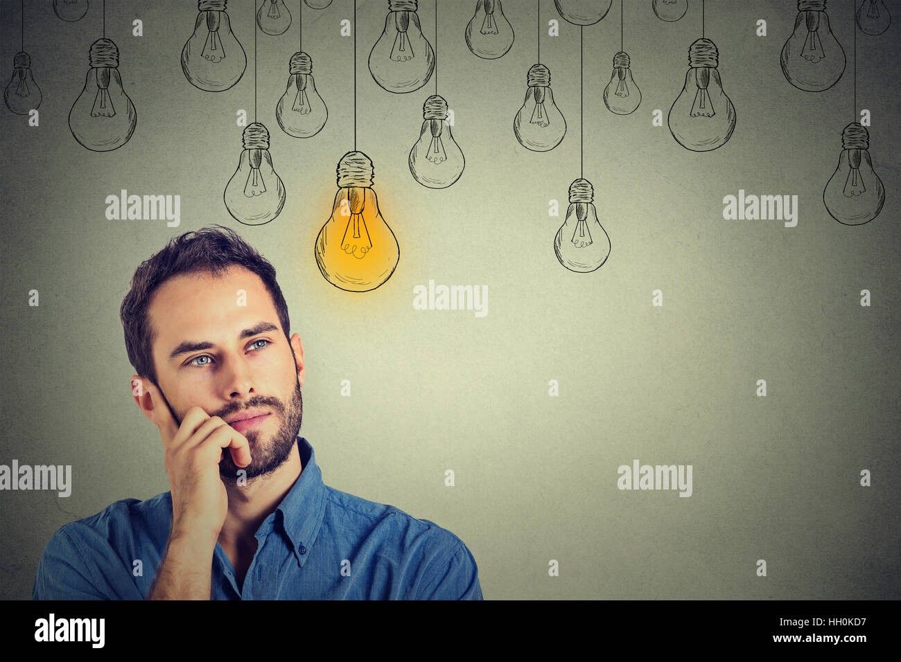 Portrait thinking handsome man looking up with idea light bulb above head isolated on gray wall background - Stock Image