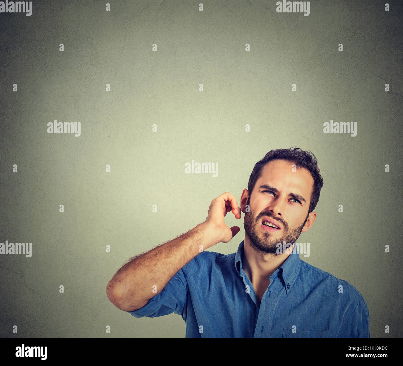 man scratching head, thinking deeply about something, looking up, isolated on gray background. Human facial expression, - Stock Image