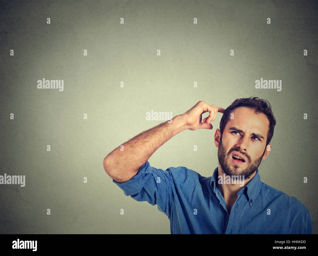 man scratching head, thinking deeply about something, looking up, isolated on gray background. Human facial expression, Stock Photo