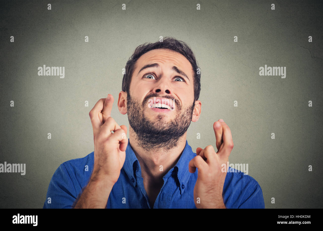 young funny guy, business man crossing fingers, wishing, hoping for best, miracle isolated on gray background. Human - Stock Image