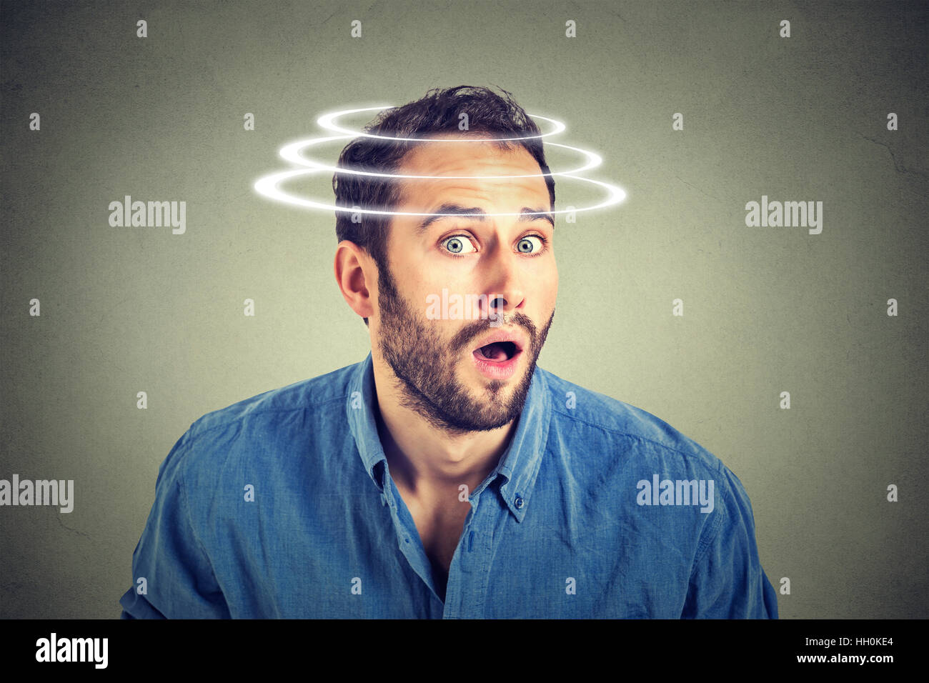 Head is spinning. Surprise astonished man. Man looking surprised in full disbelief wide open mouth isolated on gray - Stock Image