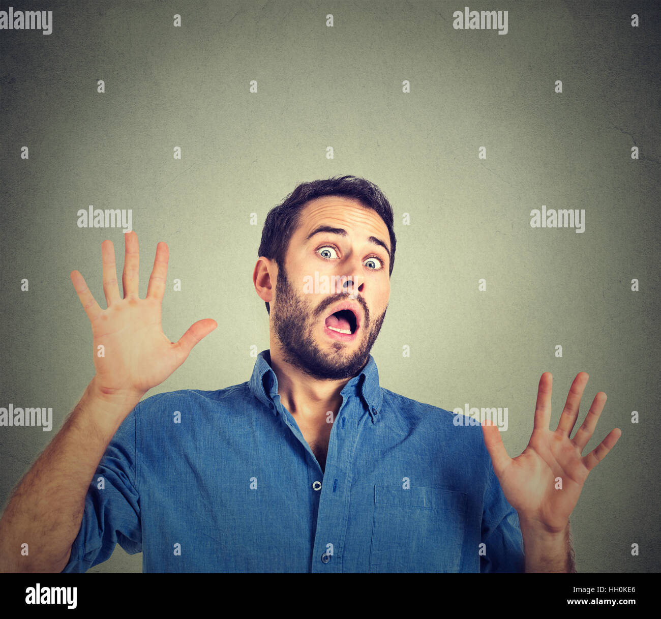 scared man on gray wall background - Stock Image