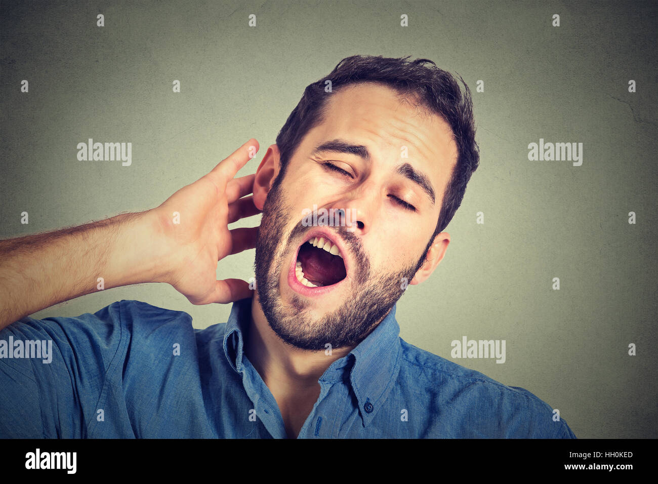 Young sleepy man yawning stretching arms back isolated on gray wall background. Sleep deprivation, burnout, laziness - Stock Image