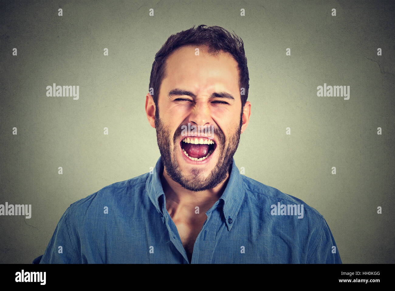 portrait of young angry man screaming - Stock Image