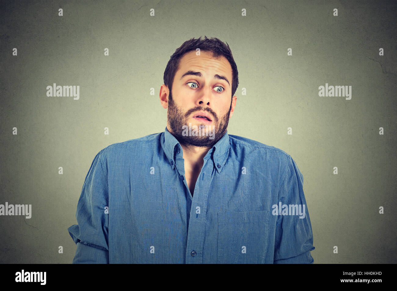 young man shrugging shoulders who cares so what I don't know gesture isolated on gray wall background. Body - Stock Image