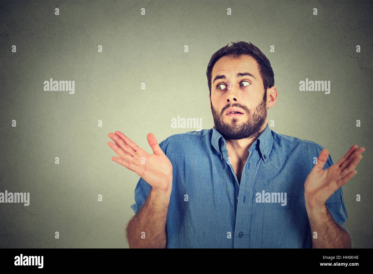 Closeup portrait young man shrugging shoulders who cares so what I don't know gesture isolated on gray background. - Stock Image