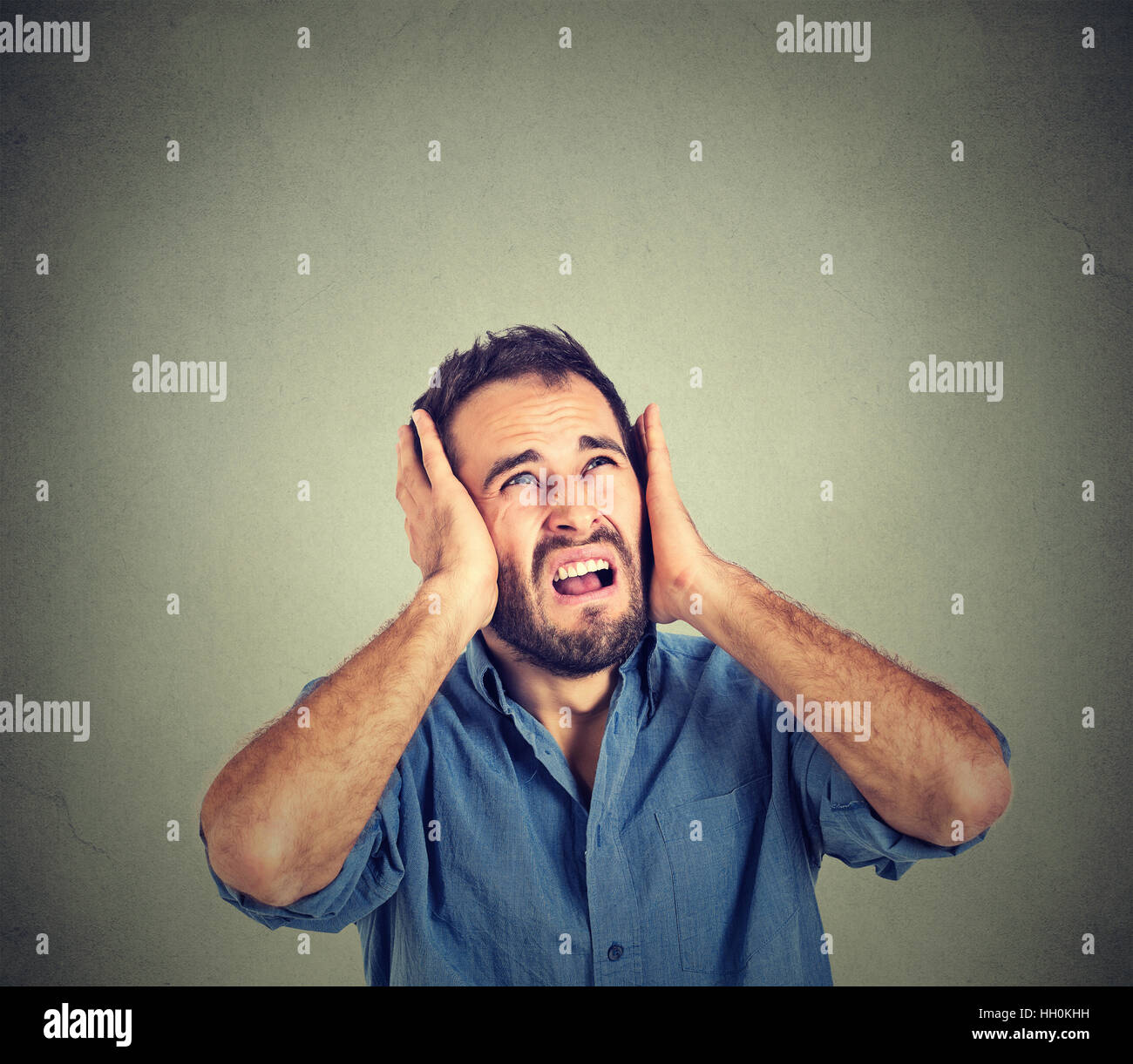annoyed unhappy, stressed man covering his ears, looking up, stop making loud noise, giving me headache isolated - Stock Image