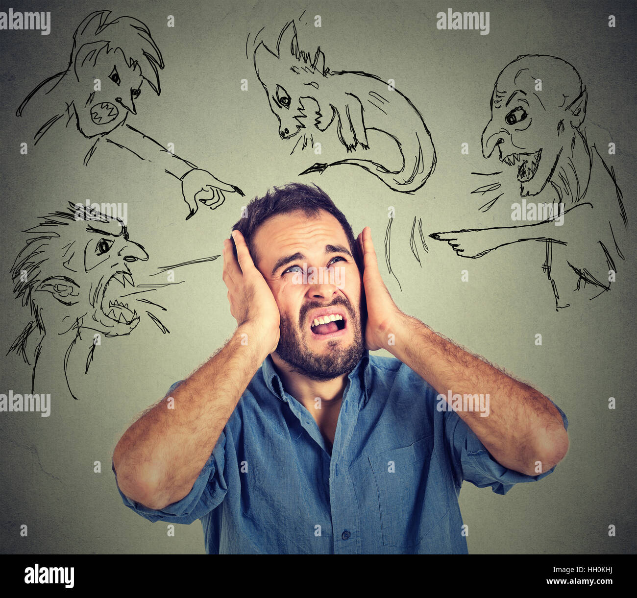Stressed young man covers his ears with his hands evil guys pointing fingers at him blaming - Stock Image