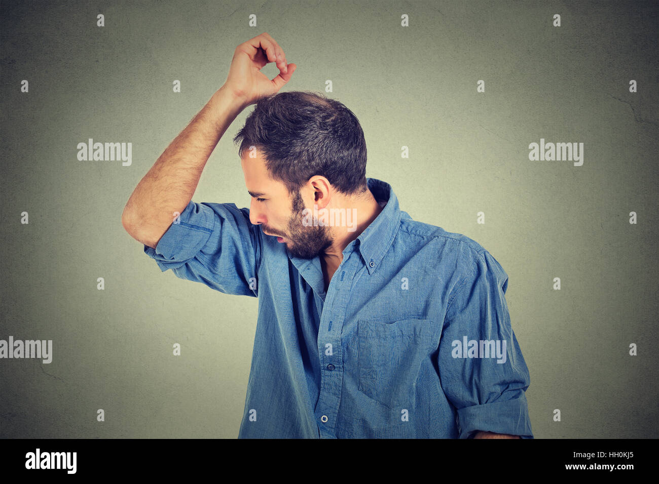 Closeup portrait of young man, smelling, sniffing his armpit, something stinks, very bad, foul odor isolated gray - Stock Image