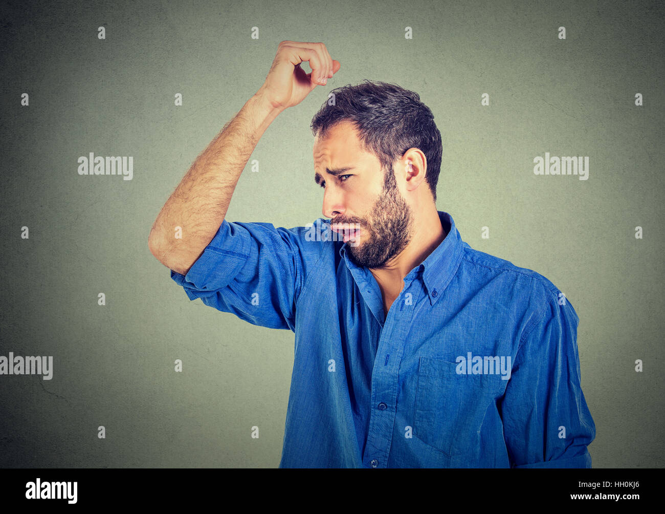 Closeup portrait of young man, smelling, sniffing his armpit, something stinks, very bad, foul odor situation, isolated - Stock Image