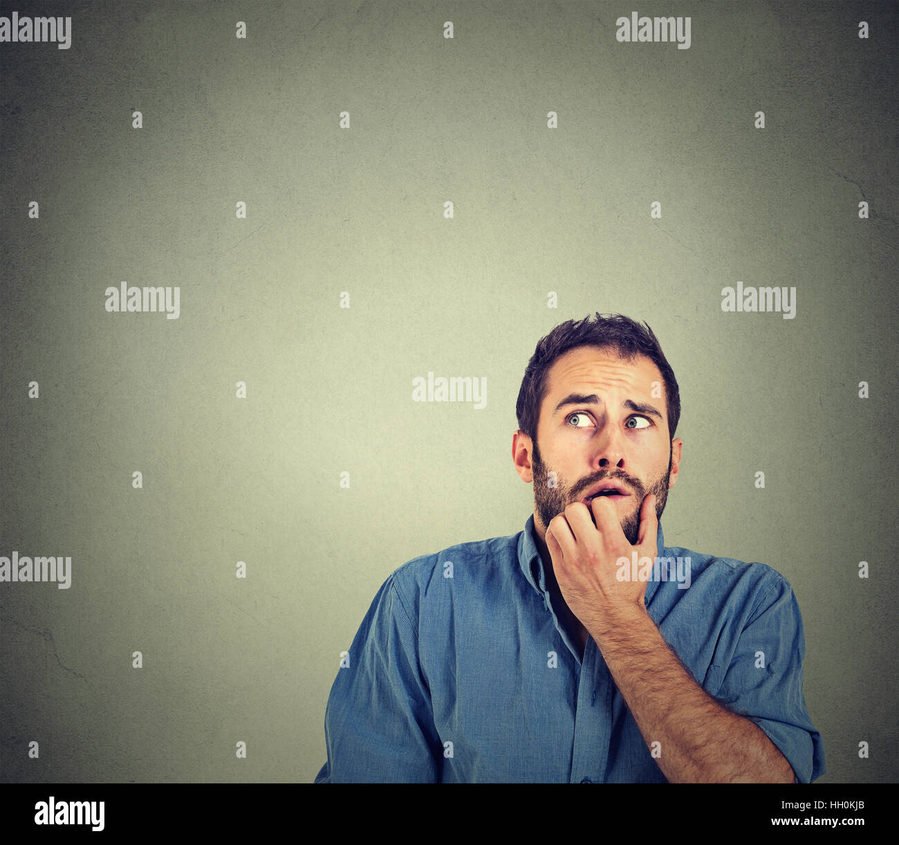 nervous stressed young man student biting fingernails looking up anxiously craving something isolated on gray wall - Stock Image