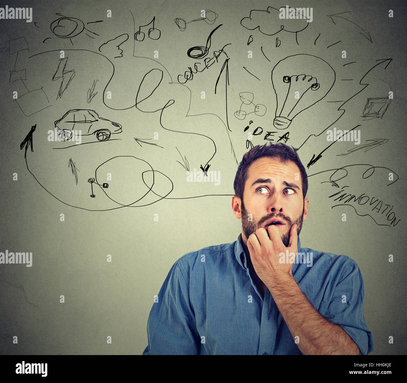 Too many things to do and plan. Worried anxious young man biting his fingernails isolated on gray wall background - Stock Image