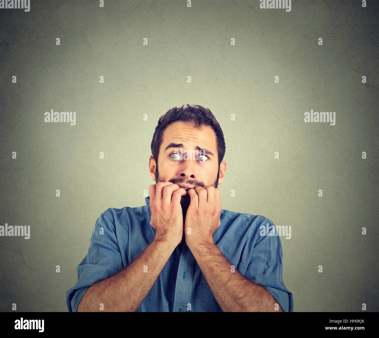 Portrait anxious young man biting his nails fingers freaking out - Stock Image