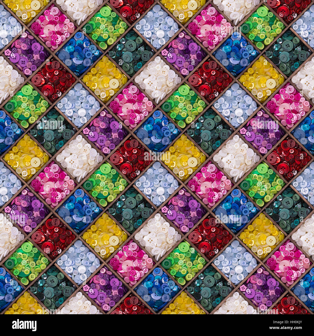 A seamless pattern of colourful buttons displayed in a wooden storage box. Tileable design suitable for wrapping - Stock Image