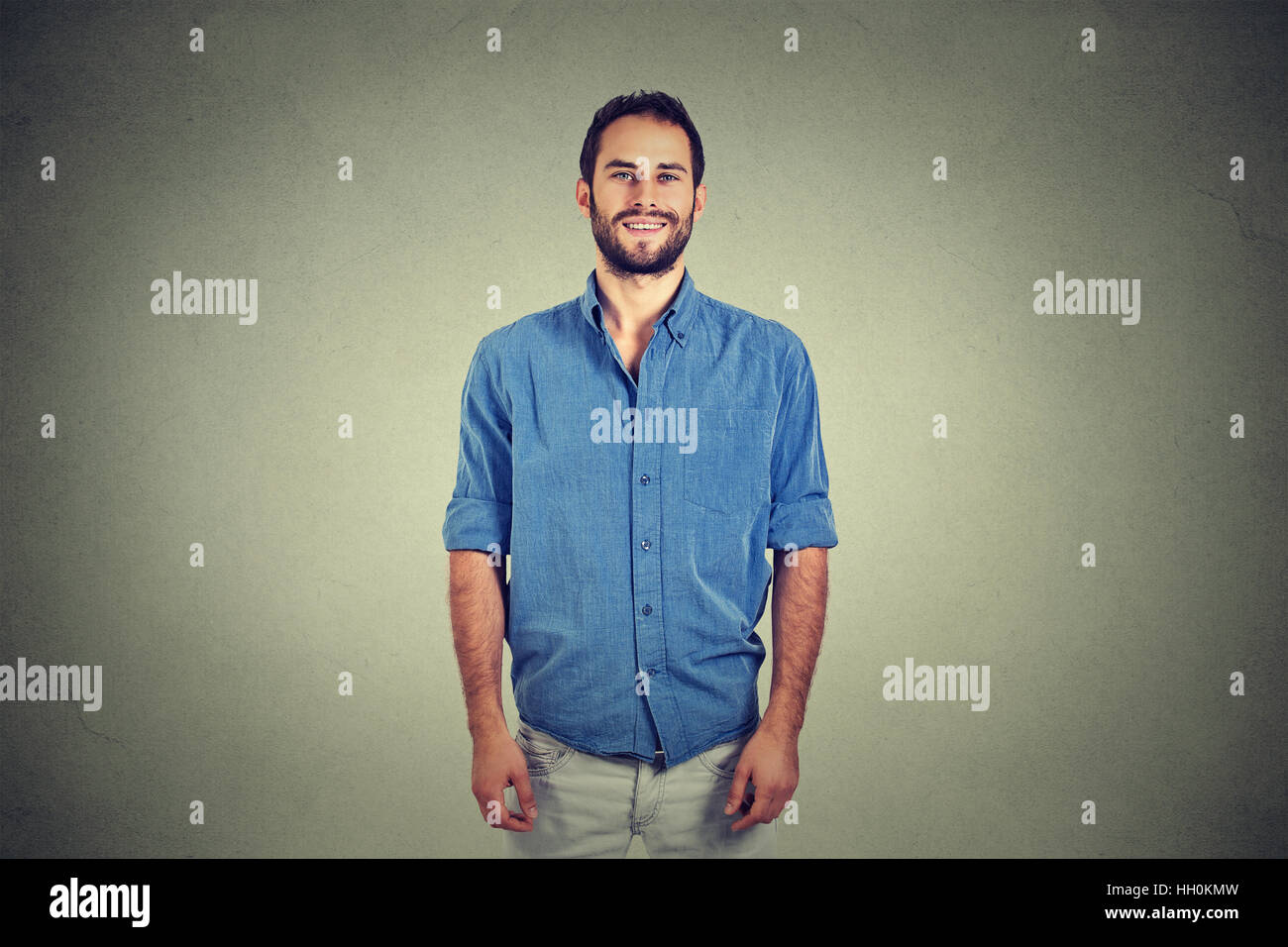 Portrait of a handsome young man smiling isolated against gray wall background - Stock Image